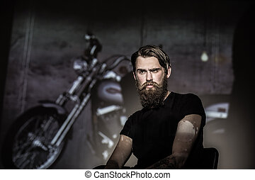Brutal angry biker on a dark background.