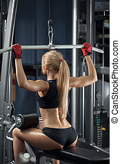 Brutal athletic woman doing back pullups at the gym
