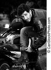 Black-and-white portrait of a sexy biker man wearing jeans and leather jacket standing relaxed by his motorcycle.