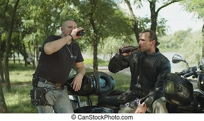 Brutal bikers drinking beer near motorbike in park - Brutal...