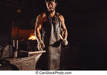 serious brutal blacksmith makes metal for future manufacturing isolated in workshop