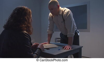 A bald policeman puts down a report folder and looks frighteningly at the criminal