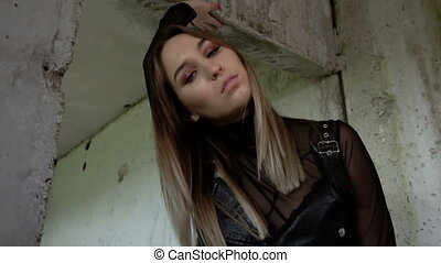 Brutal girl in an abandoned building. Model in black leather clothes