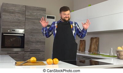Brutal man in an apron fooling around in a modern kitchen...