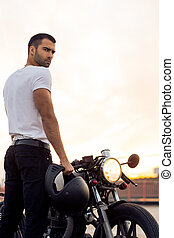 Sporty biker handsome rider man in white t-shirt want to ride his classic style cafe racer motorbike on rooftop at sunset. Vintage bike custom made in garage. Brutal urban lifestyle. Outdoor portrait.