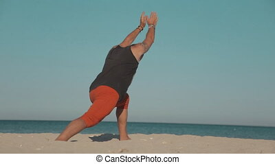 Brutal man practicing yoga at seashore