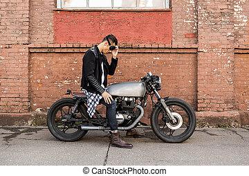 Brutal man sit on cafe racer custom motorbike.