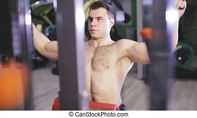 Brutal Man Using The Lat Pulldown Machine - Young Man...
