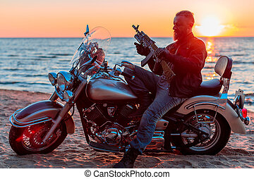 brutal man with a motorcycle on a sandy beach near the sea on a sunset background