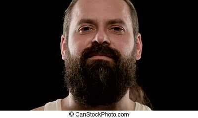 Brutal man with beard, looks at camera arrogantly. Big closeup