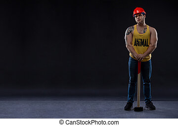 brutal Muscular worker man with a hammer