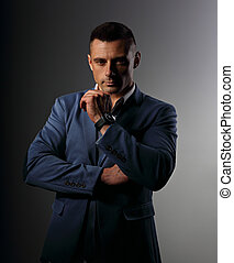 Brutal serious business man thinking in white style blue suit on grey dark background in fashion watch. Closeup portrait
