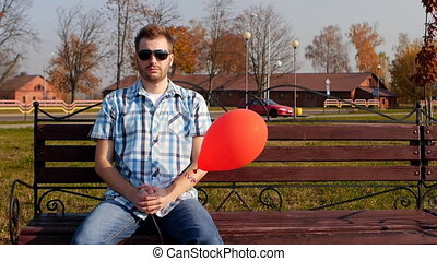 Brutal young man in black glasses sits on a bench with a red...