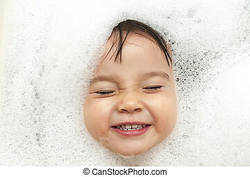 Bubble bath time - Toddler smiling showing face just above...