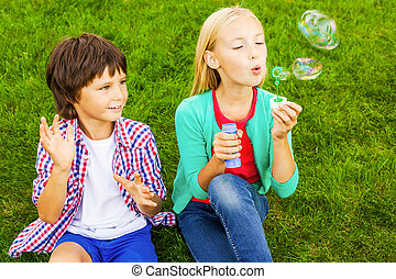 Bubble fun. Two cute little children blowing soap bubbles while sitting on the green grass together