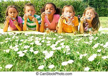 Bubble play - Portrait of cute friends having bubble fun on...