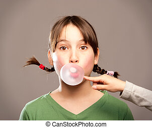 young girl making a bubble from a chewing gum