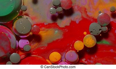 Bubbles float in liquid paint, mixing ink, oil and milk, abstract multicolor hypnotic painting
