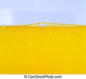 Bubbles in orange soda closeup textured background