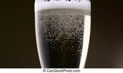 Bubbles of champagne are intensely circling in a glass....