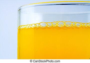 Bubbles of orange soda in a glass closeup macro textured...