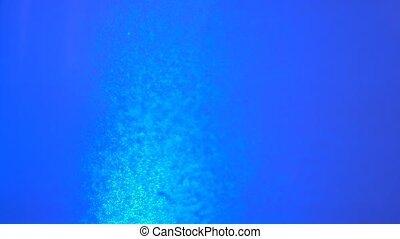 Bubbles of water boil on a blue background
