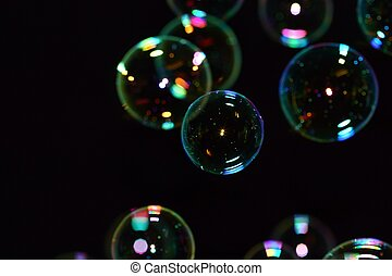 A group of soap bubbles in various stages of focus against a black backdrop. There is space to place a message or logo to the left.