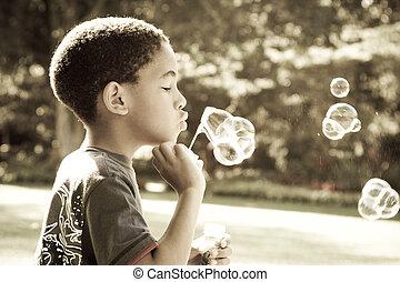 bubbles - african boy blowing bubbles in park