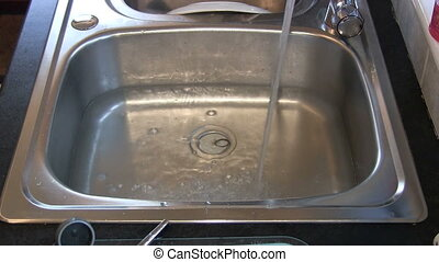 Bubbly water draining from a sink. - Bubbly water being...