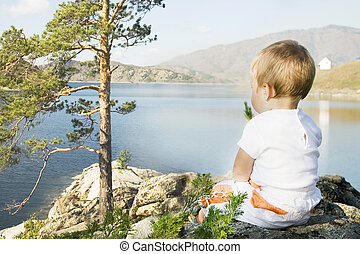 Buchtarma. Child seated on the shores of  Inlet.