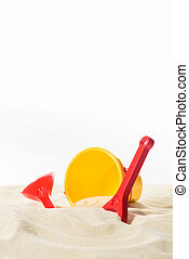 Bucket and beach toys in sand isolated on white