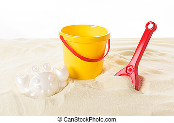 Bucket and plastic toys in sand isolated on white