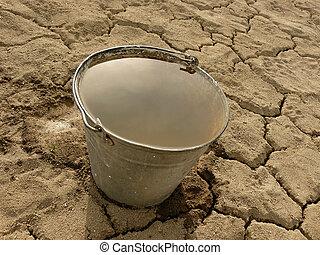 bucket full of water on dry soil background