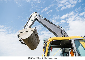 Bucket of yellow excavator loader standing against sunny cloudy sky during road construction and repairing asphalt pavement works.