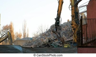 Bucket wedge-hammer excavator rakes the destroyed fragments of the building. Demolition of the building. Russia, Voronezh.