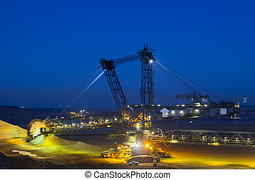 A giant Bucket Wheel Excavator at work in a lignite pit mine at night with some motion blur