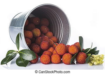 Bucket with arbutus unedo fruits over white - Bucket with...