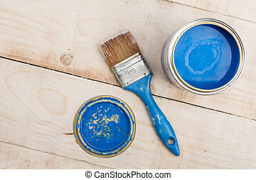 Bucket with blue color and a brush for painting on a wooden...