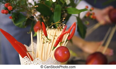 Bucket with chilli and wooden sticks for food with background of chef florists work