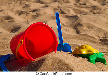 bucket with plastic beach toys in sand