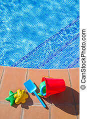 bucket with plastic beach toys near pool