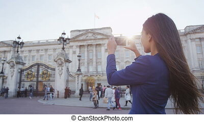 Buckingham Palace - woman taking picture of London tourist attraction on phone. Woman using smartphone taking a photograph of England top tourist destination. Young professional in blazer. SLOW MOTION