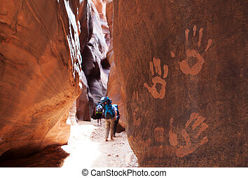 Backpackers make their way through the narrow slot canyon of Buckskin Gulch