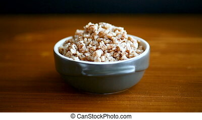 buckwheat boiled in a ceramic bowl on a wooden table