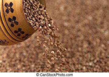 buckwheat falls from a wooden pot