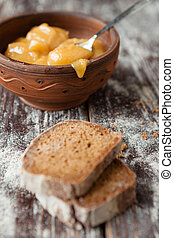 Buckwheat honey in a ceramic bowl and brown bread
