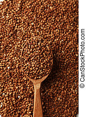 Buckwheat in a spoon on brown wooden background