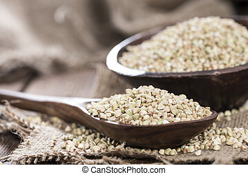Buckwheat in a Wooden Spoon on a vintage dark wooden table