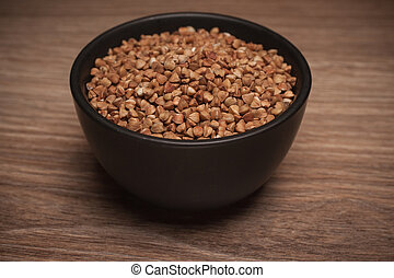 Buckwheat in black bowl on wooden background.
