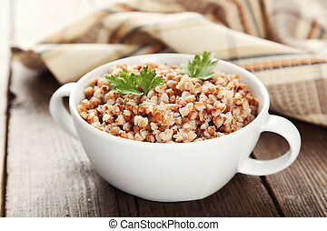 Buckwheat in bowl on brown wooden background